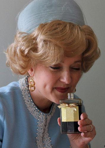 Leslie Goddard Estee Lauder powder blue suit gold earrings
